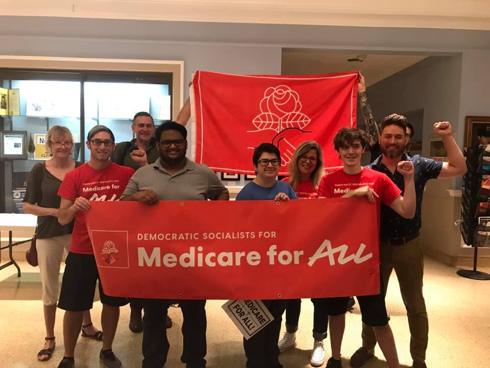 Group of people holding red Medicare For All banner